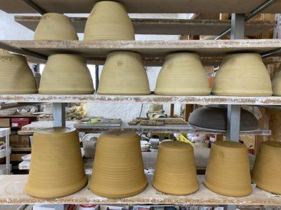 Drejade krukor på tork i keramikverkstan